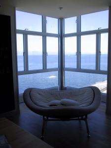 A képen egy fotel látható nagy üvegablak előtt rálátással a vízre.
