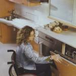 Kerekesszékben ülő hölgy kinyitja a mosogatógép ajtaját