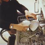 Kerekesszékben ülő hölgy kipakol a mosogatógépből