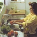 Kerekesszékben ülő hölgy zöldséget mos a csapban