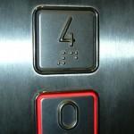 Braille illetve dombornyomott betűk alkalmazása lift gombon.