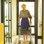 A képen a lépcsőházban egy kerekes kocsit toló idős néni látható.