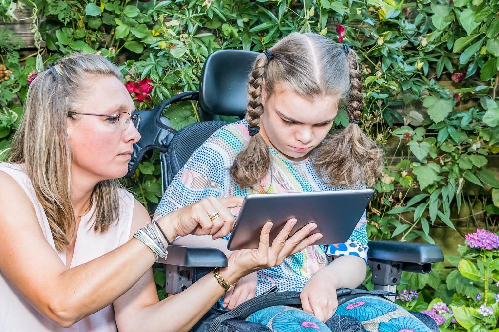 A képen egy kerekesszékben ülő lány látható, amint a felé nyújtott tableten nézi.