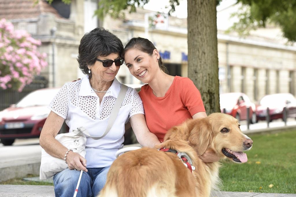 A képen egy idős látássérült hölgy fogja a kutyáját. Mellette mosolyogva hozzá bújik egy fiatal hölgy.