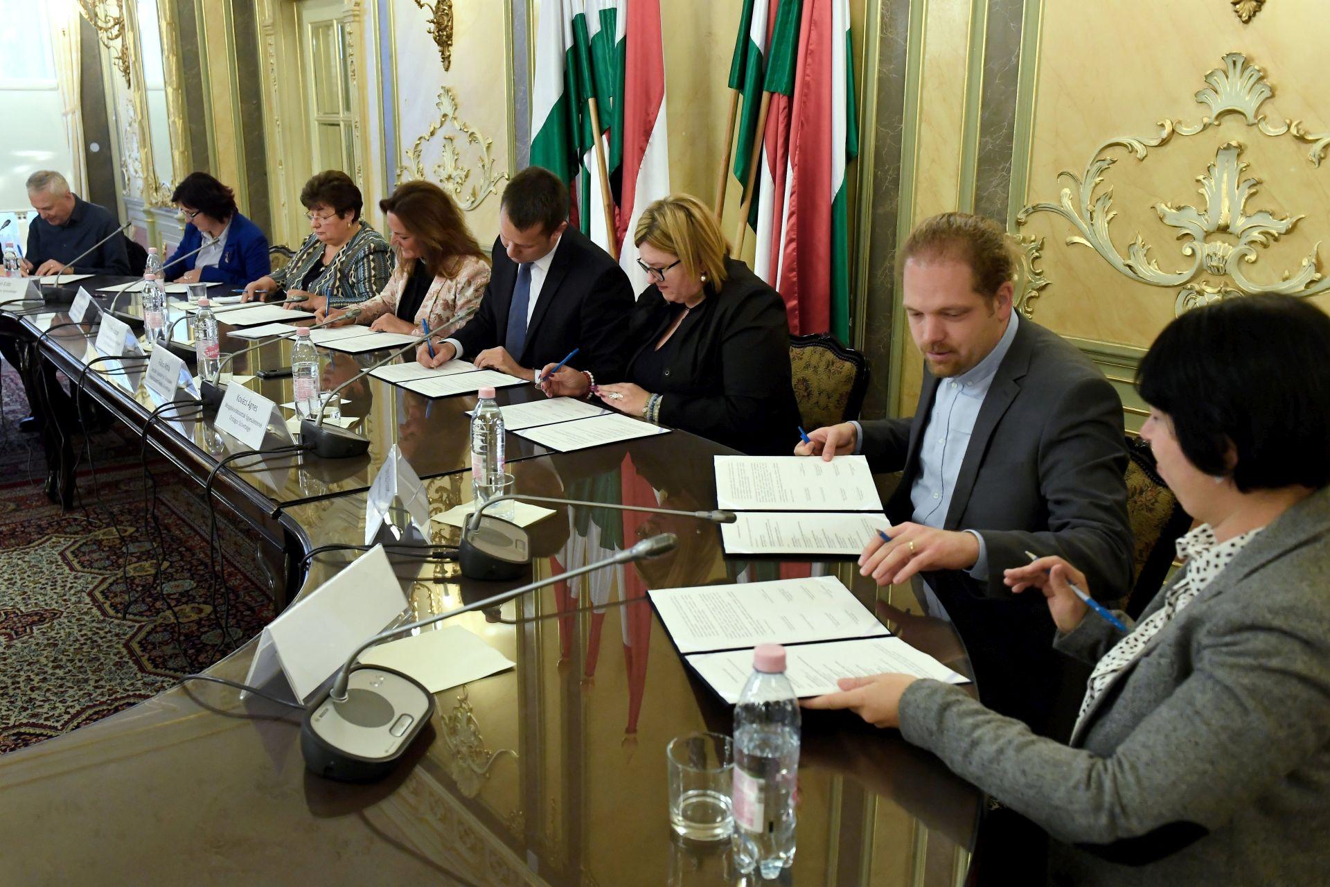 A képen az érdekvédelmi szervezetek vezetői láthatók aláírás közben.
