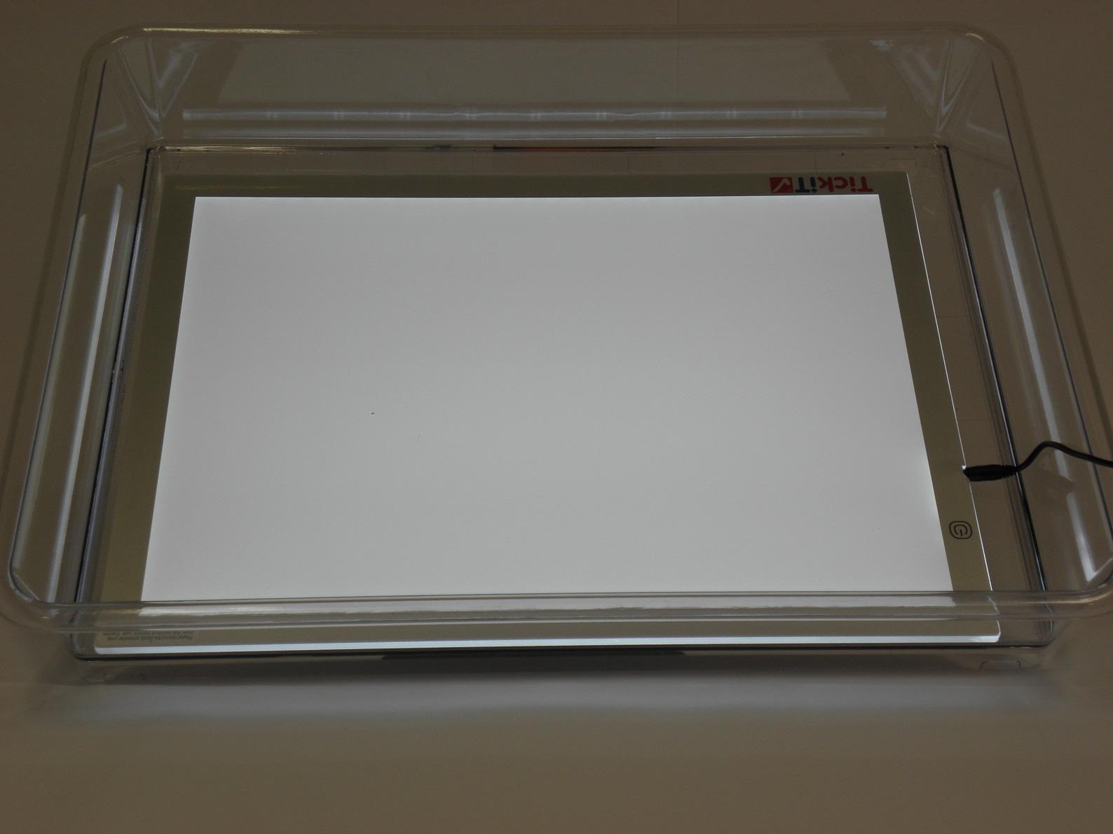 A képen egy peremmel rendelkező műanyag tálca látható, benne egy 220-as áramforráshoz csatlakoztatható, elfektetett sík képernyővel, ami világít.