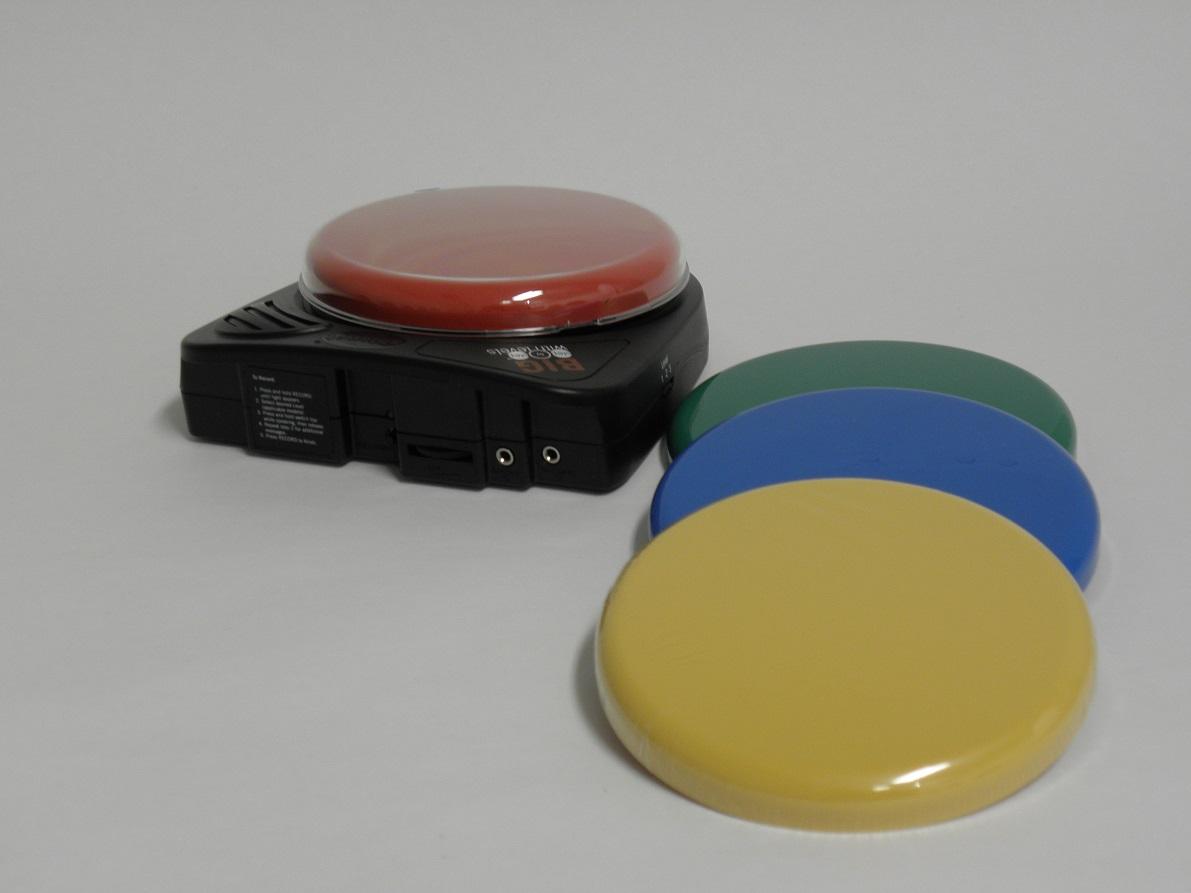 Nagy kerek piros gombbal rendelkező kommunikátor illetve a zöld, kék és sárga cserélhető tetők látszódnak a képen.